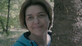 La mujer de la Edad Media se coloca cerca de árbol y de sonrisa almacen de metraje de vídeo