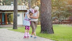 La mujer de Eldery enseña a la muchacha a patinar en pcteres de ruedas Gente mayor activa almacen de metraje de vídeo