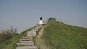 La mujer de la elegancia levanta las escaleras en hiil verde almacen de metraje de vídeo