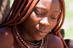 La mujer de Himba se sienta en la tierra y mira abajo Fotografía de archivo libre de regalías