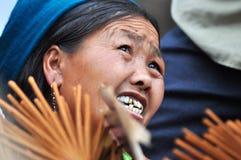 La mujer de Hmong que vende incienso se pega en el mercado de Bac Ha, Vietnam Foto de archivo libre de regalías