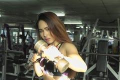 La mujer de la aptitud en el entrenamiento, demostración ejercita con pesas de gimnasia en g imágenes de archivo libres de regalías