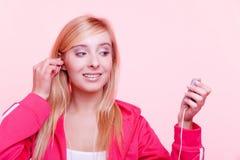 La mujer de la aptitud escucha la música mp3 relaja el gimnasio Imagen de archivo