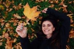 La mujer de la aptitud toma un resto en el parque de la caída Rodeado por las hojas de otoño en césped verde Foto de archivo