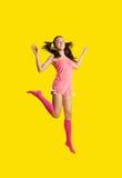 La mujer de la belleza como muchacha salta en amarillo Foto de archivo