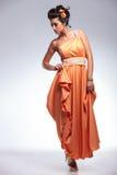 La mujer de la belleza mira abajo con la mano en el vestido Foto de archivo libre de regalías