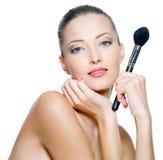 La mujer de la belleza sostiene cepillos del maquillaje Imagen de archivo libre de regalías