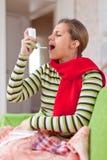 La mujer de la enfermedad utiliza el aerosol Imagen de archivo libre de regalías