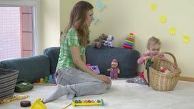 La mujer de la madre con la muchacha adorable de la hija del niño puso los juguetes en cesta almacen de video