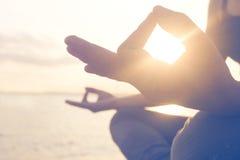 La mujer de la meditación que hace yoga ejercita orilla del mar Fotografía de archivo