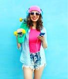 La mujer de la moda con los auriculares del monopatín escucha música en smartphone sobre azul colorido Imagen de archivo libre de regalías