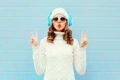 La mujer de la moda en auriculares escucha llevar de la música las gafas de sol, sombrero hecho punto, suéter sobre el fondo azul Imagen de archivo