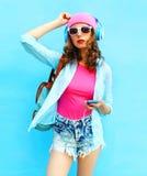 La mujer de la moda escucha la música en auriculares usando smartphone sobre azul Imagen de archivo