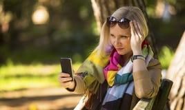 La mujer de la moda que se sienta en el parque está mecanografiando en un smartphone Imagen de archivo