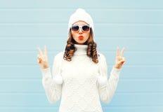 La mujer de la moda que sopla los labios rojos hace que el aire besa las gafas de sol de una forma del corazón que llevan, sombre Imagenes de archivo