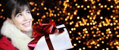 La mujer de la Navidad con el presente del paquete del regalo, y mira para arriba imagen de archivo
