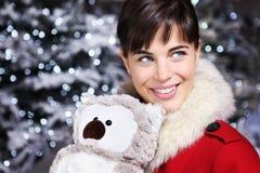 La mujer de la Navidad que sonríe con la decoración del juguete del búho, mira para arriba imagen de archivo