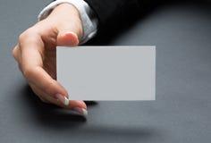 La mujer de la oficina de Youung está sosteniendo la tarjeta blanca en blanco Imagenes de archivo