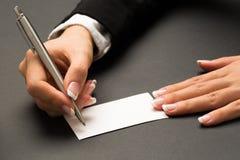 La mujer de la oficina está escribiendo con la pluma en una tarjeta blanca en blanco Foto de archivo libre de regalías