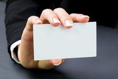 La mujer de la oficina está sosteniendo una tarjeta blanca en blanco Foto de archivo