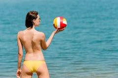 La mujer de la playa del verano goza de la bola del asimiento del sol Fotos de archivo