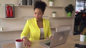 La mujer de la raza mixta trabaja en compañía del international de oficina almacen de metraje de vídeo