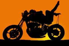 La mujer de la silueta en la motocicleta reclina los dedos del pie para arriba Imágenes de archivo libres de regalías