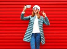 La mujer de las risas de la moda toma un autorretrato de la imagen en un smartphone Foto de archivo libre de regalías