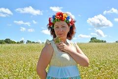 La mujer de los años medios con una guirnalda en la cabeza sostiene las flores contra la perspectiva del campo del alforfón Foto de archivo libre de regalías