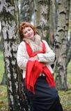 La mujer de los años medios cuesta, inclinándose contra un abedul en la madera Imagenes de archivo