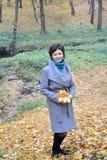 La mujer de los años medios se coloca cerca de una corriente en parque del otoño Foto de archivo