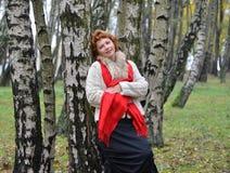 La mujer de los años medios se ha inclinado contra un abedul en la madera Imagen de archivo libre de regalías
