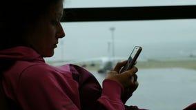 La mujer de los deportes utiliza smartphone por la ventana del aeropuerto Aeroplano en el fondo metrajes