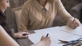 La mujer de los diseñadores de Clother crea un bosquejo en el papel a su cliente en estudio del sastre almacen de video