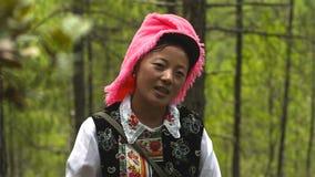La mujer de los tibetanos en el pueblo de Jidi, se sienta en el centro del área de la producción del matsutake en Shangri-La yunn fotografía de archivo