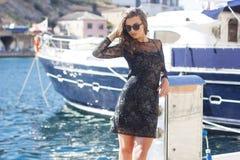 La mujer de lujo está caminando en bahía cerca de los barcos Foto de archivo libre de regalías