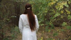 La mujer de mediana edad caucásica pelirroja en una capa blanca camina en un día nublado en el parque del otoño metrajes