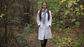 La mujer de mediana edad caucásica pelirroja en una capa blanca camina en un día nublado en el parque del otoño almacen de metraje de vídeo