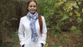La mujer de mediana edad caucásica pelirroja en una capa blanca camina en un día nublado en el parque del otoño almacen de video