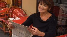 La mujer de mediana edad discute la nueva edición del periódico almacen de video