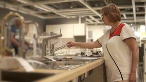La mujer de mediana edad está intentando los grifos en zona comercial en tienda al por menor grande metrajes