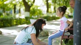 La mujer de mediana edad le está enseñando a pcteres de ruedas de la hija en parque metrajes