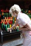 La mujer de mediana edad pone una vela en lugar santo Foto de archivo libre de regalías