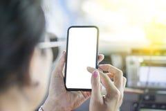 La mujer de mediana edad que llevan las gafas de sol está sosteniendo el teléfono móvil a mano fotografía de archivo