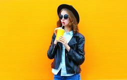 La mujer de la moda bebe el zumo de fruta en chaqueta negra de la roca en la ciudad imágenes de archivo libres de regalías