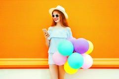 La mujer de la moda con los globos coloridos de un aire está utilizando el smartphone Imágenes de archivo libres de regalías