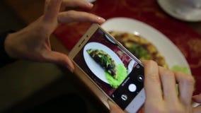 La mujer de moda en un restaurante hace la foto de la comida con la cámara del teléfono móvil para la red social almacen de metraje de vídeo