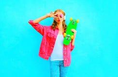 La mujer de la moda escucha la música en los auriculares inalámbricos sostiene el monopatín en una chaqueta rosada del dril de al Foto de archivo libre de regalías