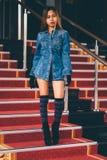La mujer de moda joven en tejanos, y la rodilla rayada larga pega caminar abajo en las escaleras con la alfombra roja Foto de archivo libre de regalías