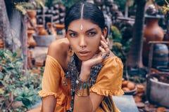 La mujer de moda joven hermosa con compone y los accesorios elegantes del boho que presentan en fondo tropical natural fotos de archivo